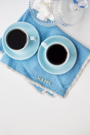 Two blue coffee cups on blue napkin with the words happy