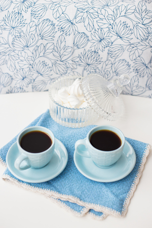 Two blue coffee cups on blue napkin and saucer with marshmallow