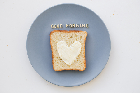 bacon love: sandwich for breakfast in the form of heart with cheese on a blue plate inscription good morning
