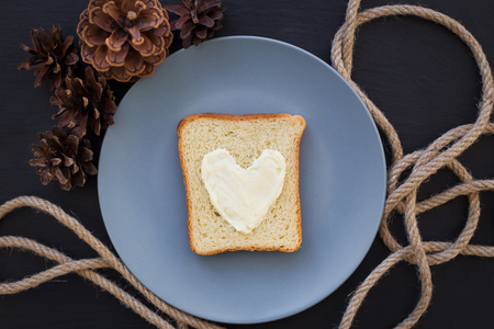 bacon love: sandwich for breakfast in the form of heart with cheese on a blue plate and black background with cones
