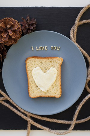 bacon love: sandwich for breakfast in the form of heart with cheese on a blue plate and black background with cones inscription I love you