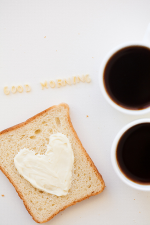 sandwich for breakfast in the form of heart with cheese - good morning sign and two coffee cups
