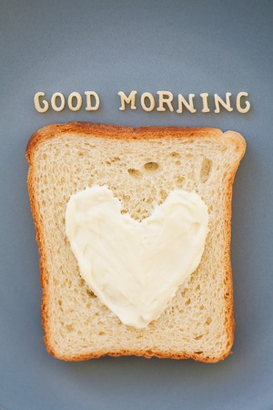 bacon love: sandwich for breakfast in the form of heart with cheese on a blue plate inscription good morning, close-up
