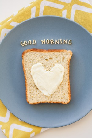 bacon love: sandwich for breakfast in the form of heart with blue cheese on a plate and napkin bright inscription good morning Stock Photo