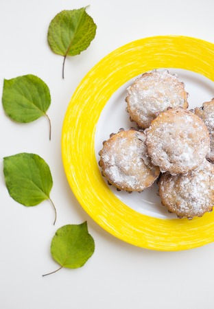 cup four: Beautiful cakes with powdered sugar on a yellow plate