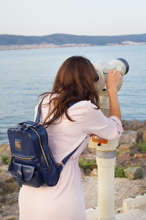The girl looks through the telescope at the sea Stock Photo