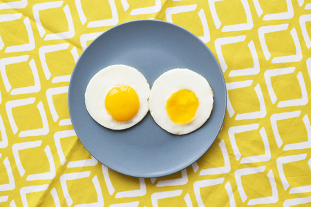 two eggs on a plate and a yellow napkin Stock Photo