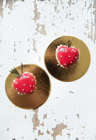 Beautiful and tasty dessert in the form of heart on an old wooden background.