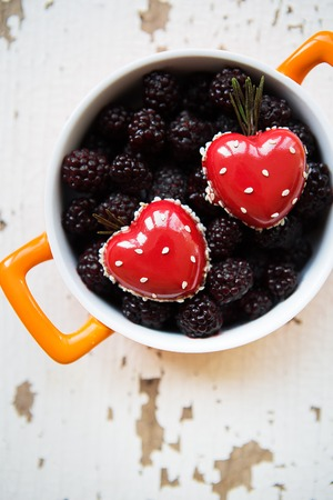 A full blackboy plate with a dessert in the form of a heart stands on a wooden background, close-up. Stock Photo