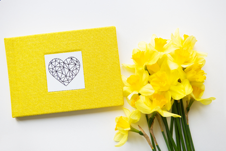 Yellow bouquet of daffodils and yellow book on white table.