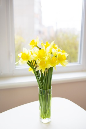 Posy of bright yellow daffodils on white wooden table. Stock Photo