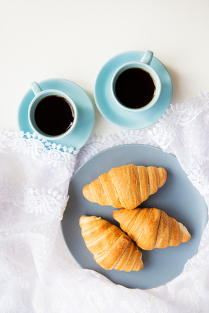 two cups of coffee with croissants on the background laces Stock Photo