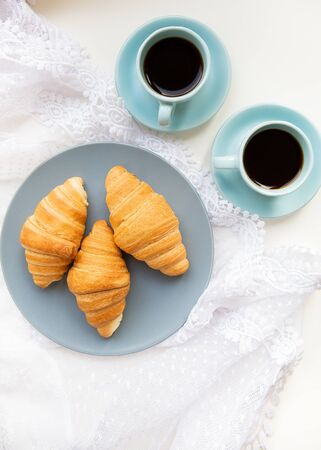 two cups of coffee with croissants on the background of laces, close-up Stock Photo