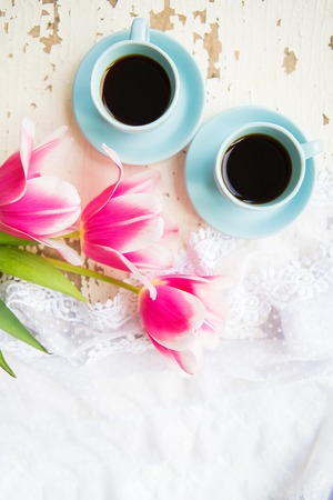 two cups of coffee and pink tulips on an old table.