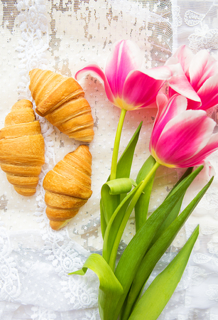 Three croissants and bright pink tulips on lace tablecloth.