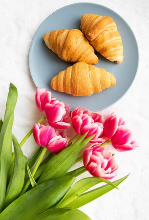 croissants on the background of laces on a white background with a bouquet of pink tulips.