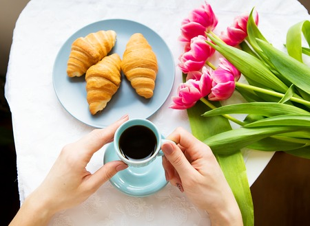 Girl with croissants and coffee, a bouquet of pink tulips, happy morning.