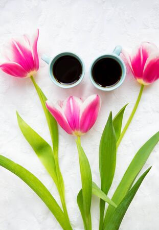 two cups of coffee and a bouquet of pink tulips. Stock Photo