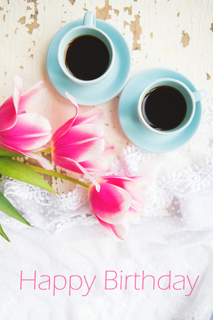 two cups of coffee and pink tulips on an old table, writing happy birthday.