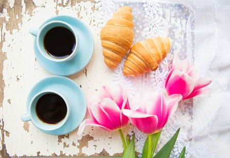 nice cup of coffee, croissants and pink tulips on old white table. Stock Photo