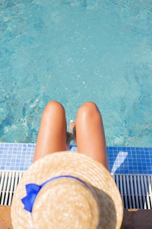 Beautiful girl in a hat near a blue pool - sun, summer, heat.