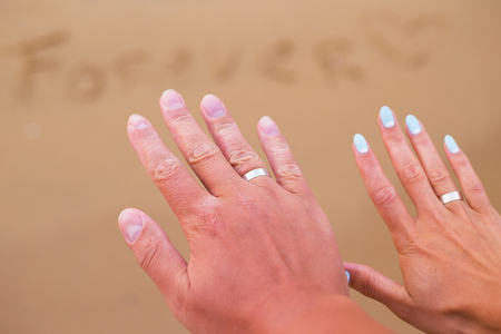 The inscription on the sand forever on the background of the hands of a young couple. Stock Photo