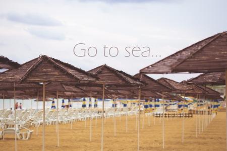 Umbrellas straw on the beach-inscription go to the sea.