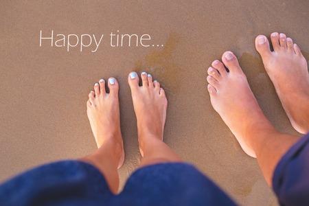 Feet of two lovers on sand-summer, sun, sea, beach, inscription happy time.