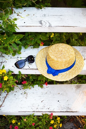 A straw hat and glasses on a wooden staircase are surrounded by greenery.
