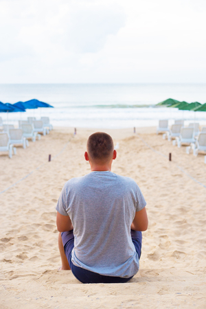 Young guy sits with his back on a sandy beach.
