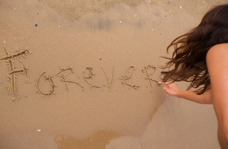 The girl is writing an inscription on the sand-forever. Stock Photo