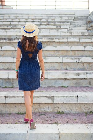 Beautiful girl on the steps in a blue dress and hat. Stock Photo