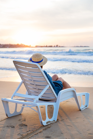 Beautiful girl in a hat sits on a deckchair meeting the dawn.