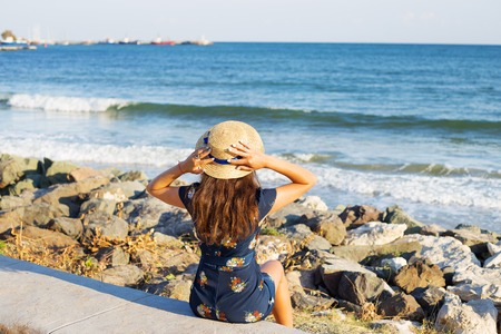 Beautiful girl in a hat sits near the sea on stones.