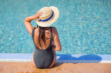 Beautiful girl in a black swimsuit near a blue pool-summer, sun, vacation.