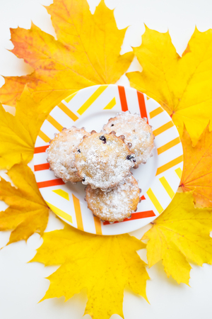 colored cupcakes on a plate and yellow autumn leaves Stock Photo