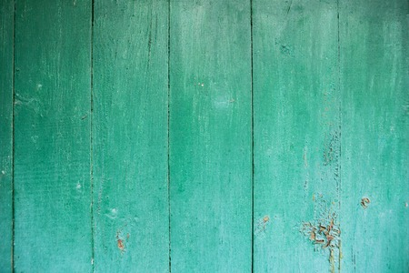 Shabby and very old green-blue wooden fence.