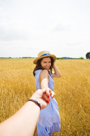 a girl in a blue dress is standing with her back in a wheat field.