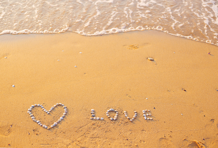 On the sand shells lined with heart and the word love. Imagens