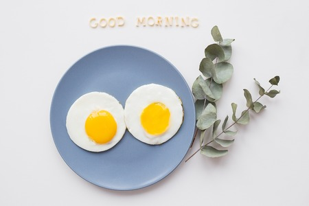 two eggs on a plate with a sprig of eucalyptus, an inscription good morning