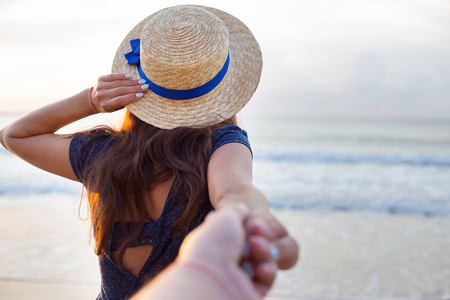 Beautiful girl in a hat holds a hand of a guy.