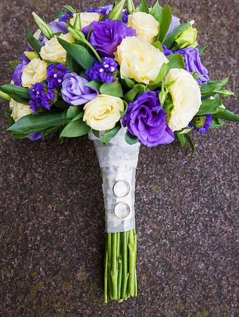 bridal bouquet of purple and beige colors and wedding rings 版權商用圖片