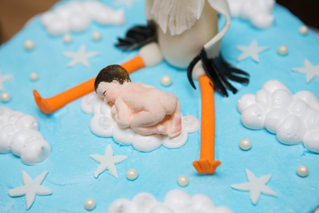 bright blue baptismal cake with baby and stork, close-up.