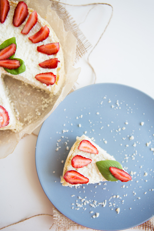 Bright cheesecake decorated with fresh strawberries and basil leaves, cut one piece on a plate.