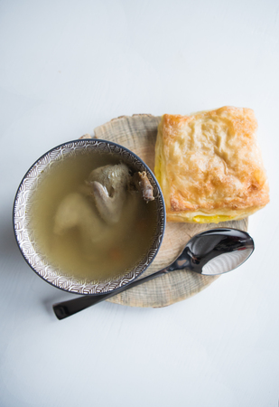 Soup with quail stands on a wooden stand along with pastries.