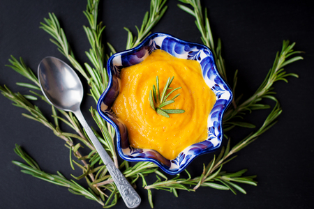 pumpkin soup on a black background with the sprigs of rosemary, close-up Stock Photo