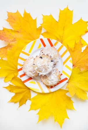 colored cupcakes on a plate and yellow autumn leaves, close-up