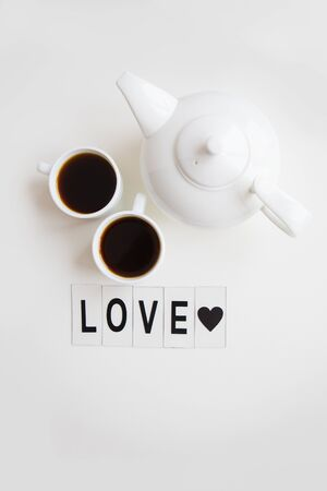 two cups of coffee on the table with a teapot, inscription love.