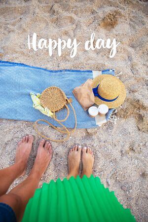 Picnic by the sea. A blue plaid on which are glasses with coffee, a bag, a hat. Feet of a couple in love. Inscription happy day