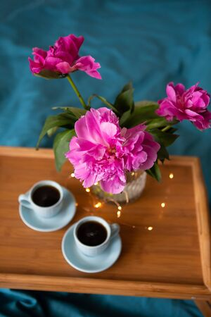 Beautiful pink peonies and two cups of coffee are standing on a wooden tray in bed. Close-up.